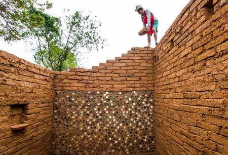 adobe wall: Builder building earthen house by earthen brick. Stock Photo