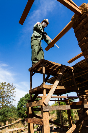 adobe wall: Builder sawing wooden roof for earthen house.