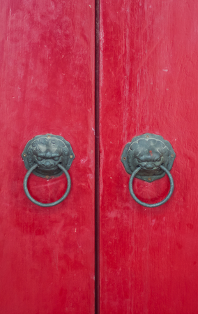 Wooden red vintage door with lion head brass decoration.
