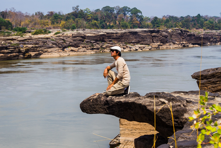 Traveller relaxing on the cliff beside Mekong river. Stock Photo