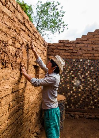Builder plastering wall in earthen house.