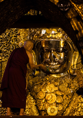 am: MANDALAY,MYANMAR-MARCH 7: Early morning the senior monk presenting the offering to Mahamyatmuni Buddha in Mahamyatmuni temple on March 7,2017 in Mandalay,Myanmar.The ritual of daily face washing Mahamyatmuni Buddha every morning at 4 am .