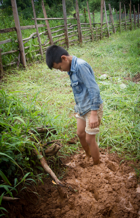 The boy mixing  ingredient of earthen house by feet. Stock Photo