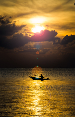Silhouette of fisherman rowing the boat while sunset.