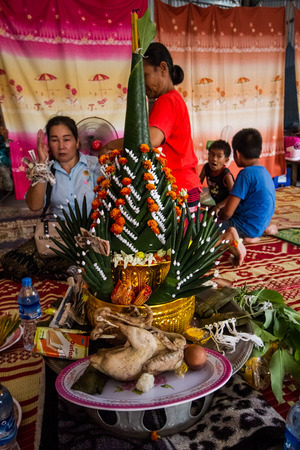 SAVANNAKHET,LAOS-APRIL 7 ,2019 :Laos new year ceremony  the guest will tie thread around hand for house owner. .This ceremony believed will make happiness  for house owner.