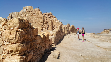 Masada is an ancient fortification in the Southern District of Israel situated on top of an isolated rock plateau, akin to a mesa. It is located on the eastern edge of the Judaean Desert, overlooking the Dead Sea 20 km east of Arad. Editorial
