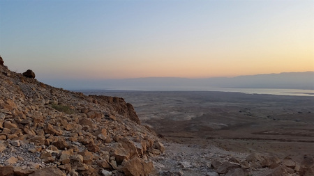 Masada is an ancient fortification in the Southern District of Israel situated on top of an isolated rock plateau, akin to a mesa. It is located on the eastern edge of the Judaean Desert, overlooking the Dead Sea 20 km east of Arad. Stock Photo