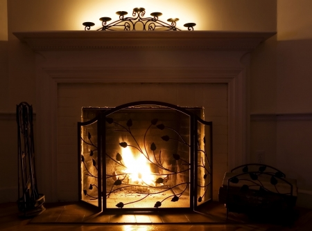 Fireplace with burning logs and candles on the mantle Stock Photo