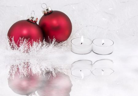 Candles and red Christmas ornaments surrounded by snowy tinsel and ice photo