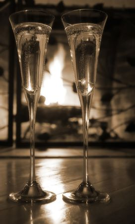 Champagne glasses with engagement ring in front of the fireplace.  Selective focus, sepia tone photo