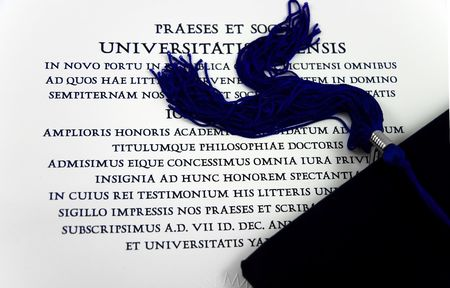 Black graduation hat with tassel over diploma in Latin Stock Photo - 2284051