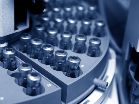 analytical chemistry: Capped vials on an analysis autosampler - selective focus, blue tinting