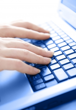 Female hands typing on keyboard - High key image with selective focus photo