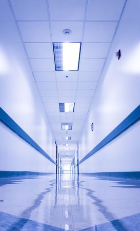 impersonal: Long, empty corridor in a hospital or office building, with the ceiling lights reflected on the shiny floor. Stock Photo