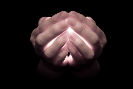 Hands holding a glowing candle, with light pouring through the fingers that appear translucent.  Muted tones.
