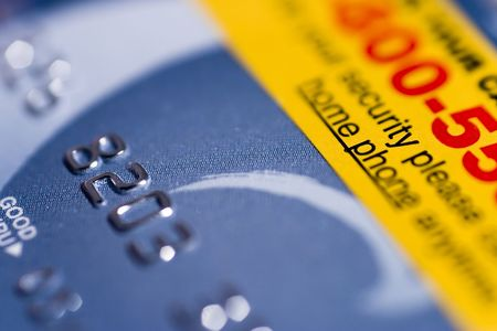 activation: Close up of brand new credit card, with activation reminder sticker attached.  Shallow depth of field, focusing on the words  Stock Photo