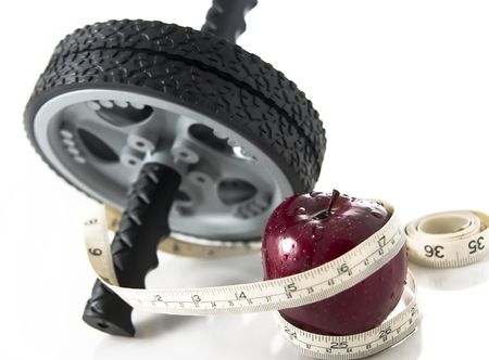 Fresh appetizing red delicious apple and ab wheel wrapped together with with a measuring tape. Slight reflection, white background, shallow depth of field with focus on the apple