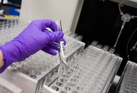 Gloved hand of scientist picking up a test tube 免版税图像