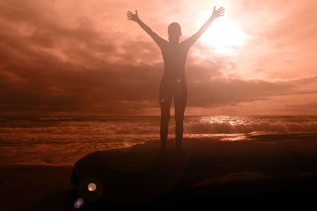 victory: Fiery glory - woman with arms raised on a fiery sunset seascape with dramatic clouds Stock Photo