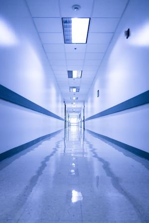 Long, empty corridor in a hospital or office building, with the ceiling lights reflected on the shiny floor Stock Photo - 2338145