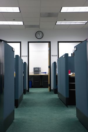 Empty cubicles in an office, clock on the wall showing lunchtime Stockfoto