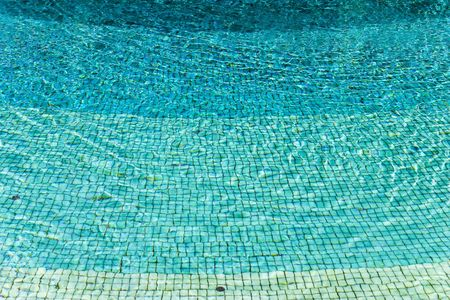 clear blue water over paterned tile pool floor Stock Photo