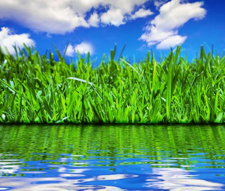 Brilliant emerald grass with beautiful cloudy summer sky reflected in calm water Stock Photo - 2338239