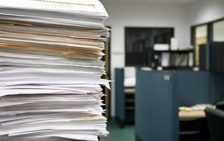 impersonal: Pile of papers on a background of office cubicles.  Selective focus at the corner of the papers