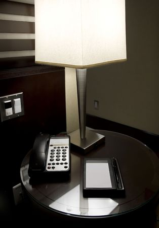 lit lamp: Lit lamp and writing instruments on hotel desk. Ambiance light. Stock Photo
