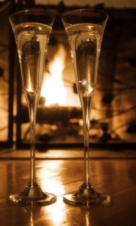 engagement ring: Champagne glasses with engagement ring in front of the fireplace.  Selective focus, gold tone