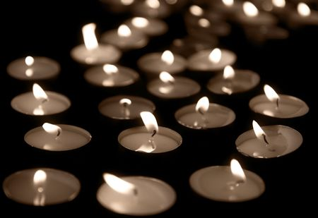 candlelight memorial: Burning tea lights on black background, with selective focus, sepia toning