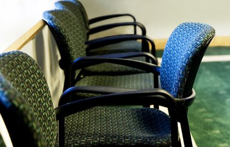 conform: Standing out - one chair standing out in a row of office chairs - selective focus on