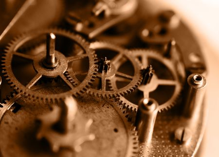 insides: Workings of time - close-up of old clock mechanism, shallow depth of field, sepia color