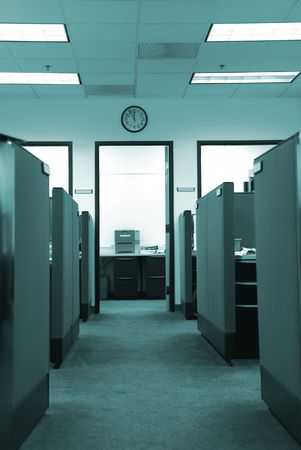 Empty cubicles in an office, clock on the wall showing lunchtime Stock Photo