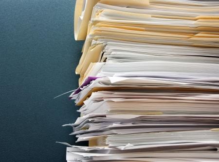 messy office: Pila di documenti nei confronti di un cubicolo testurizzati parete verde Archivio Fotografico