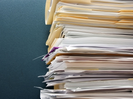 paperwork: Pile of paperwork against a textured green cubicle wall