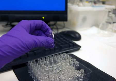 analytical chemistry: Gloved hand of scientist holding up a vial, with a computer terminal in the background.  Showing integration of chemistry, biology or medicine with computer science.  Shallow depth of field, focus on the vial