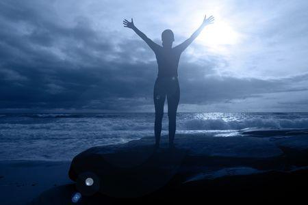 gratitudine: Mezzanotte gloria - silhouette femminile a braccia sollevate, in una torbida notte al chiaro di luna, con l'oceano