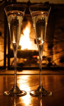 Champagne glasses with engagement ring in front of the fireplace.  Selective focus, gold tone