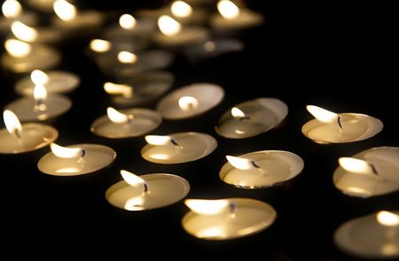 candlelight memorial: Burning tea lights on black background, with selective focus