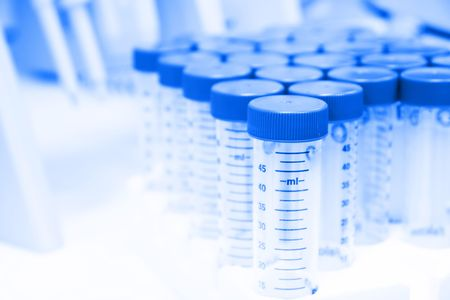 Group of centrifuge tubes on a biology bench, with pipettes in the background.  Selective focus, high key, blue tint Stock Photo