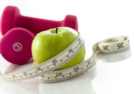 pesas: Fresca y apetitosa manzana de colores brillantes pesas atado con una cinta m�trica. Gira a la reflexi�n, fondo blanco, se centran en la manzana