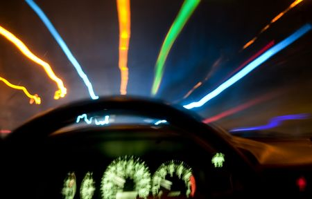 causing: Long exposure photo from the drivers seat, with colorful street lights.  Car shake causing blur on the speedometer