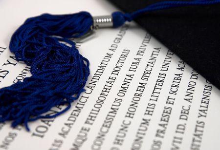 Black graduation hat with tassel over diploma in Latin 免版税图像