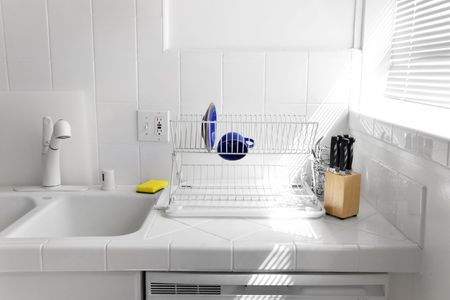 spotless: Pristine white tiled kitchen counter with light streaming through window blinds Stock Photo