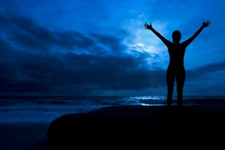 Midnight glory - female silhouette with arms raised, in a cloudy moonlit night, by the ocean