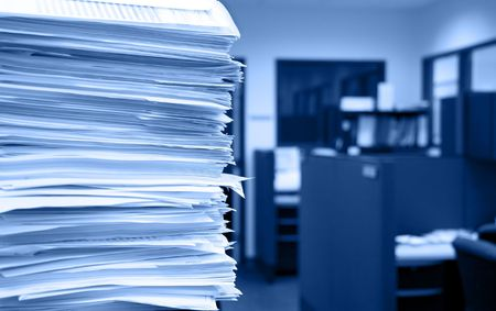 Pile of papers on a background of office cubicles.  Selective focus at the corner of the papers.  Blue tint