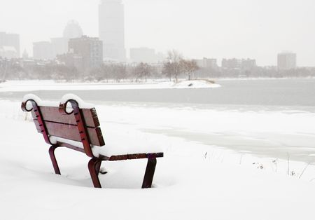 Bench in the snow on Charles River in Boston photo