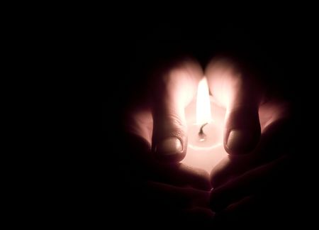 Hands holding a lit canle - low key image, warm colors Stock Photo - 2438345