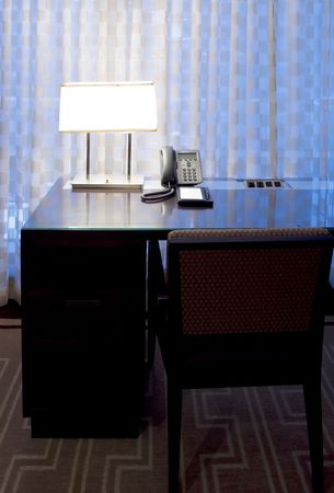 lit lamp: Lit lamp and writing instruments on hotel desk. Dusk light coming through the delicate curtains Stock Photo